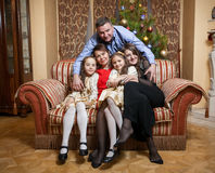 Father hugging big family seated on sofa at christmas day Stock Photo