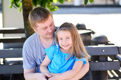 Father hugging daughter on the bench in the park on sunny summer day stock photography