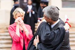 Father hugging daughter graduation. Middle aged father hugging daughter at graduation ceremony stock photography