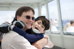 Father hugging disabled son on  ferry boat Royalty Free Stock Images