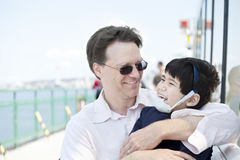 Father hugging disabled son on  ferry boat Stock Photos
