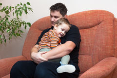 Father hugging his child. Happy father hugging his child, sitting on sofa at home Royalty Free Stock Images