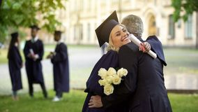 Father hugging his graduate daughter giving flowers, congratulating, paternity. Stock photo stock photos