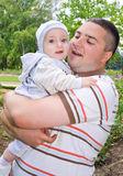 Father hugging his little son. A young father hugging his little son in the park Stock Image