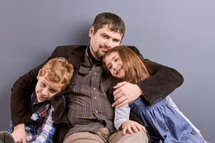 Father hugging his son and daughter. Studio shot of caring father sitting with two kids. Happy father and joyful kids. Concept of family happiness Stock Photography