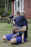 Father hugging his son. The vertical summer picture of the father hugging his son royalty free stock images