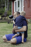 Father hugging his son. The vertical summer picture of the father hugging his son Stock Photo