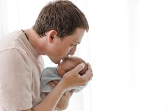 Father hugging and kissing his newborn child. Close-up portrait of happy young father hugging and kissing his sweet adorable newborn child. Indoors shot, concept royalty free stock image
