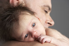 Father Hugging Newborn Baby. With head resting on shoulder royalty free stock image