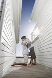 Father Hugging Son In Passageway Between Houses. Side view of happy father hugging son in passageway between beach houses Royalty Free Stock Photography