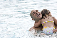 Father hugging young daughter in swimming pool. Father hugging 2 year old daughter in swimming pool royalty free stock images
