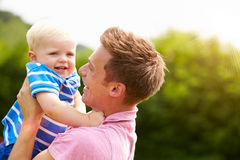 Father Hugging Young Son In Garden Stock Images