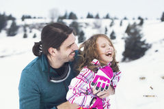 Father hugs his daughter affectionately in the snow. In mountain Royalty Free Stock Photography