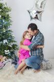 Father hugs his daughter, New Year`s mood. Father hugs his daughter, tender hugs, New Year`s mood, new year interior royalty free stock image