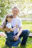Father hugs his little daughter. Dad and daughter are sitting together in a city park royalty free stock photos