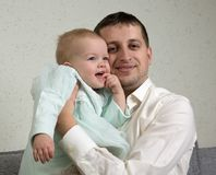 The father hugs little daughter who holds her finger in her mouth stock image
