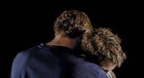 Father hugs young son after argument. Father holds preteen son close - reconciliation, love - in a moody portrait stock images