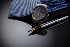 Father& x27; imagen del día de s o del concepto del negocio Man& elegante x27; reloj de s, pluma y lazo azul en fondo negro de la fotografía de archivo libre de regalías