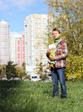 Father with infant baby in sling, full growth. On the background of the urban landscape, autumn Royalty Free Stock Photography