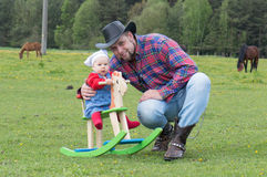 Father with infant daughter cowboy style Royalty Free Stock Image