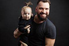 Young athletic father with adorable baby on black background. Father and infant daughter posing with different grimaces at studio black background witj copyspace stock photo