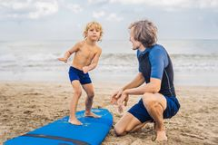Father or instructor teaching his 4 year old son how to surf in royalty free stock photos