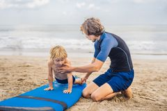 Father or instructor teaching his 4 year old son how to surf in the sea on vacation or holiday. Travel and sports with. Children concept. Surfing lesson for stock images