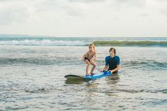 Father or instructor teaching his 4 year old son how to surf in the sea on vacation or holiday. Travel and sports with. Children concept. Surfing lesson for stock image