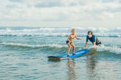Father or instructor teaching his 4 year old son how to surf in the sea on vacation or holiday. Travel and sports with. Children concept. Surfing lesson for stock photos