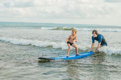 Father or instructor teaching his 4 year old son how to surf in the sea on vacation or holiday. Travel and sports with. Children concept. Surfing lesson for royalty free stock photography