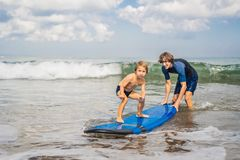 Father or instructor teaching his 4 year old son how to surf in stock photography