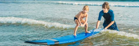 Father or instructor teaching his 4 year old son how to surf in the sea on vacation or holiday. Travel and sports with. Children concept. Surfing lesson for royalty free stock images