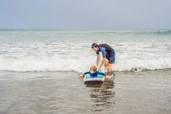 Father or instructor teaching his 5 year old son how to surf in the sea on vacation or holiday. Travel and sports with. Children concept. Surfing lesson for royalty free stock photo