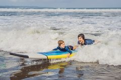 Father or instructor teaching his 5 year old son how to surf in the sea on vacation or holiday. Travel and sports with. Children concept. Surfing lesson for stock image