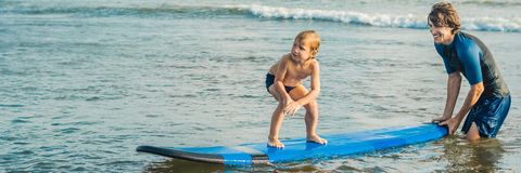 Father or instructor teaching his 4 year old son how to surf in the sea on vacation or holiday. Travel and sports with stock image