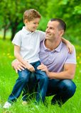 Father keeps son on the knee. In the green park. Concept of happy family relations and carefree leisure time Royalty Free Stock Image