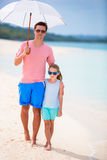 Father and kid at beach with umbrella hiding from sun Stock Photography