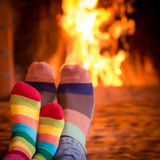 Father and kid near fireplace. Father and kids feet in Christmas socks near fireplace. Family relaxing at home. Winter holiday concept Stock Photo