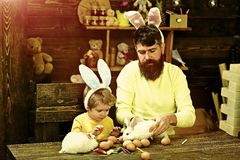 Rabbit`s family with bunny ears. Father and kid painting Easter eggs. Rabbit`s family with bunny ears. Cute little child boy wearing on Easter day stock photos