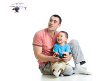 Father and kid playing with RC helicopter toy Royalty Free Stock Image