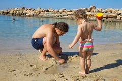 Father and kid playing with sand at the beach. Royalty Free Stock Images