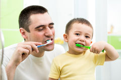 Father and kid son brushing teeth Stock Image