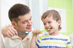 Father and kid son brushing teeth in bathroom. Father and kid brushing teeth in bathroom royalty free stock photography