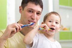 Father and kid son brushing teeth in bathroom Royalty Free Stock Photo