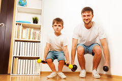 Father and kid son workout with dumbbells together Royalty Free Stock Photography