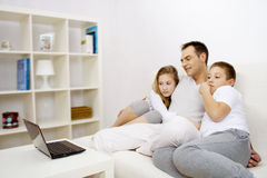 Father with kids. Father watchin film on laptop with kids Stock Photography