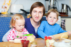 Father and kids baking. Father and two kids baking pie at kitchen together stock photography