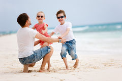 father on beach with kids