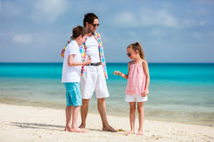 Father with kids at beach Stock Images