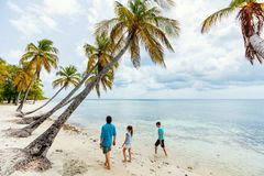 Father with kids at beach. Father and kids enjoying beach vacation on tropical island royalty free stock image